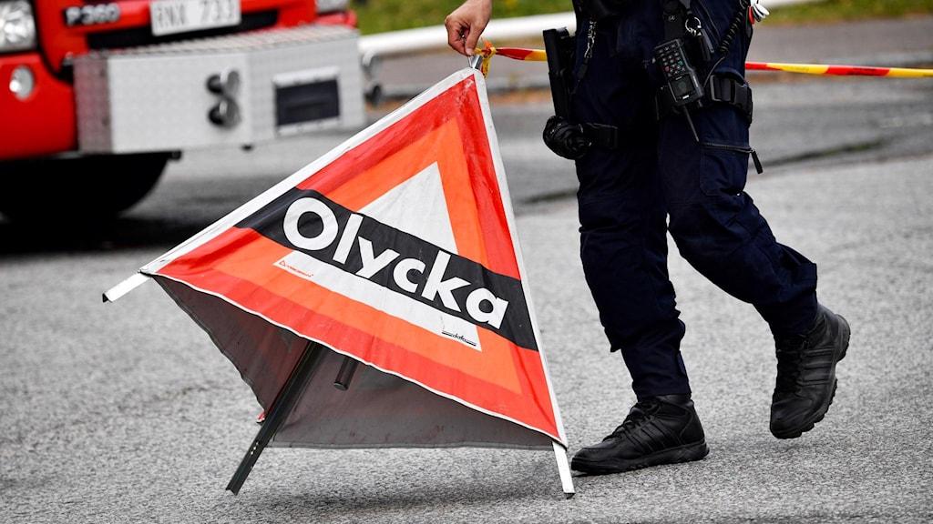 polis håller i olycksskylt. Foto: Johan Nilsson/ TT.