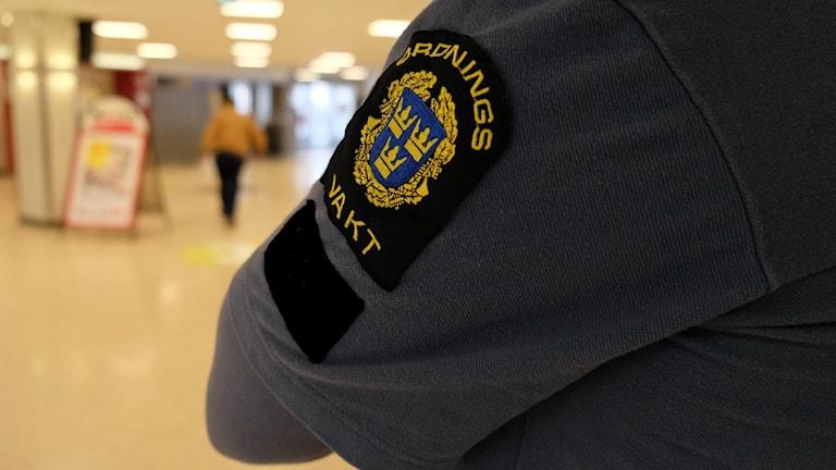 En ordningsvakt står och övervakar en galleria.