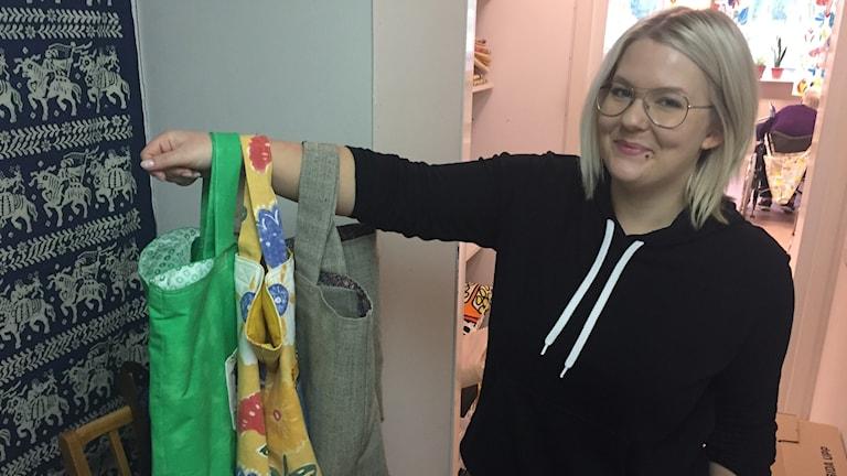 Johanna Carli visar upp tygkassar som Kristina Pihlblad har sytt.