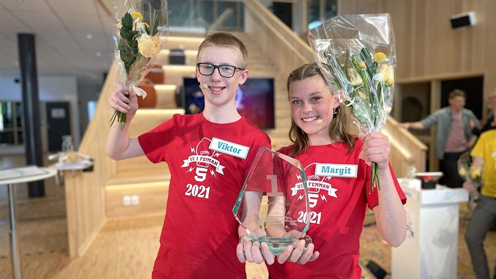 Viktor Berg och Margit Klintenberg poserar med blommor och pris efter vinsten i Vi i femman.