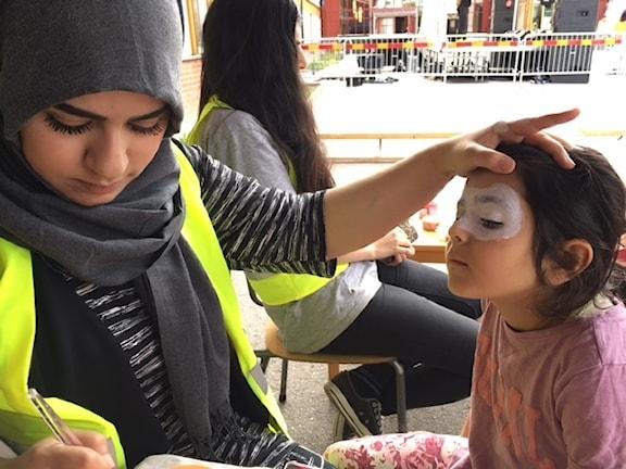 Hajir Alrikabi gör ansiktsmålning på Sara, 5 år.