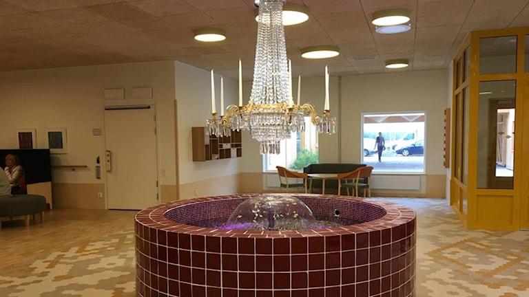 I ett av rummen på det nya äldreboendet finns en fontän med en kristallkrona ovanför.
