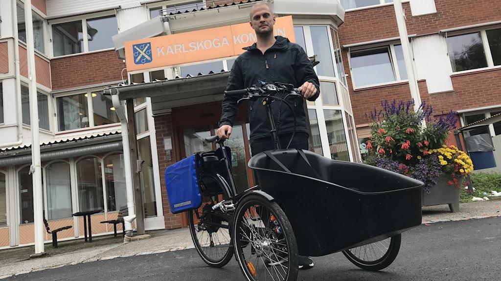Bild på Daniel Eklund som står bakom en lastcykel.