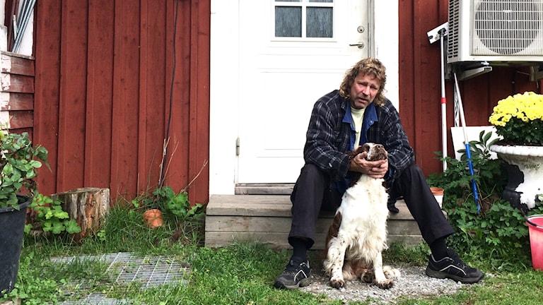 Marko Lappalainen sitter framför ett hus med sin hund.