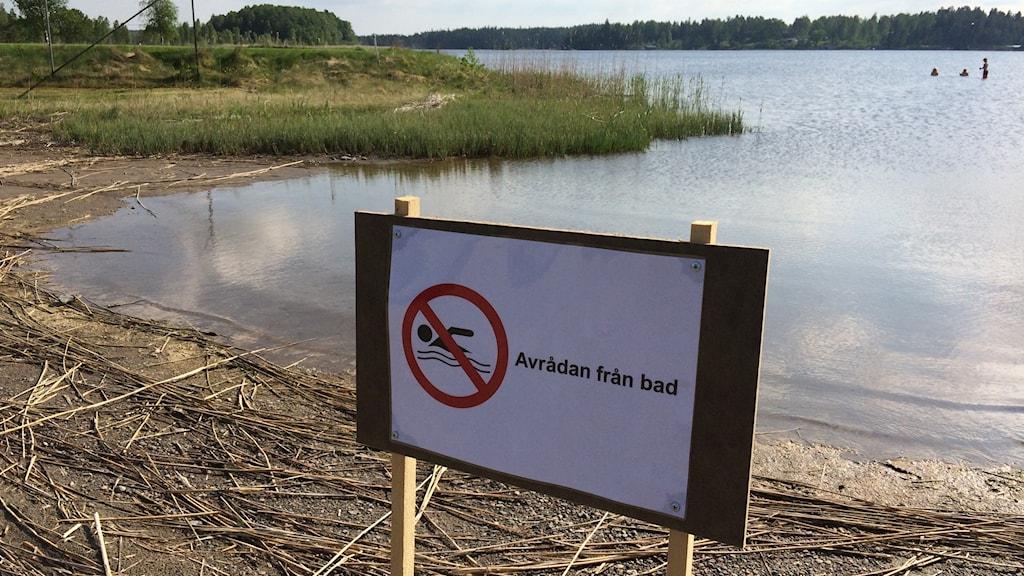 skylt som avråder från bad framför badplats
