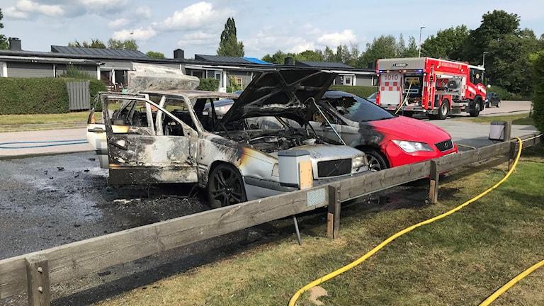 Två bilar på en parkering kraftigt skadade av en brand. I bakgrunden en brandbil