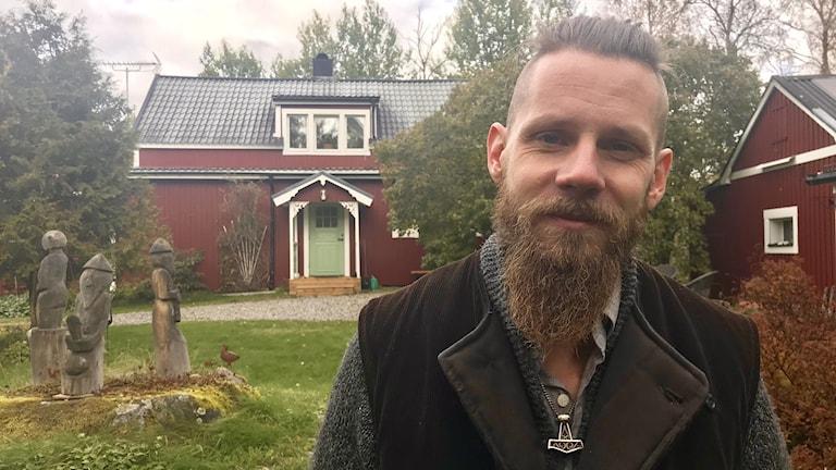 Johan Sandström med sina motorsågsfigurer i bakgrunden, föreställande Tor, Frej och Freja.