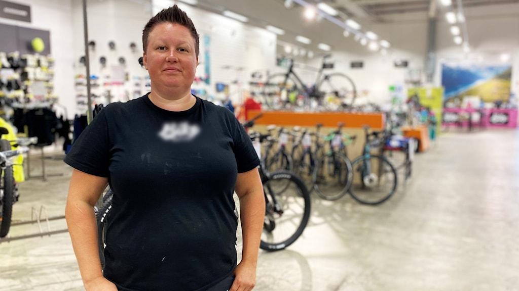 Bild på Camilla Eriksson, tillförordnad butikschef på en cykelbutik i Örebro. Kort mörkt hår och har en svart t-shirt på sig. I bakgrunden finns det cyklar uppställda.