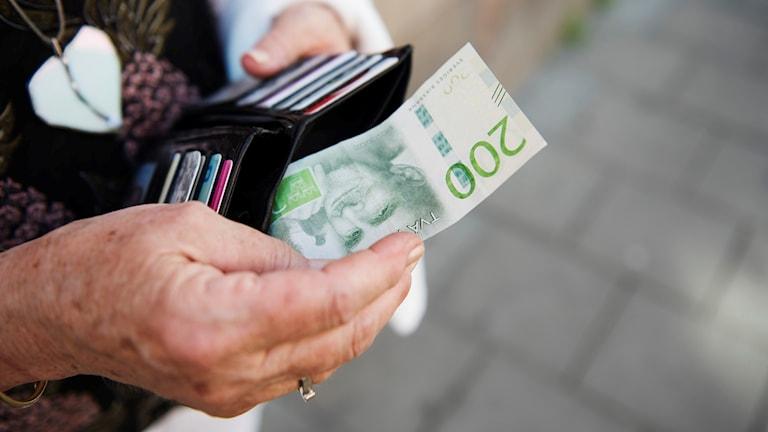 En kvinna håller upp en plånbok med pengar
