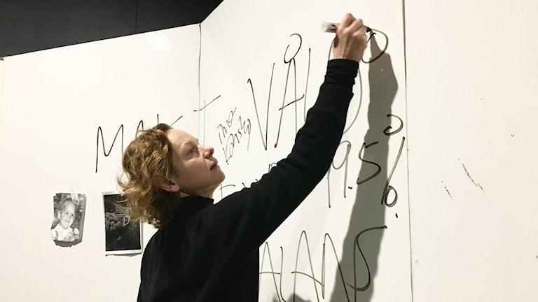 Hanna Lekander skriver ord som makt och våld på väggen.