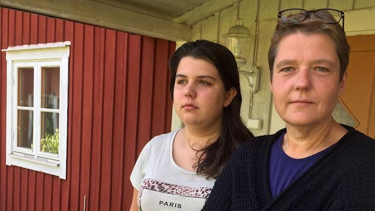 Emelie och Åsa Jansson står utanför ytterdörren på sitt hus.