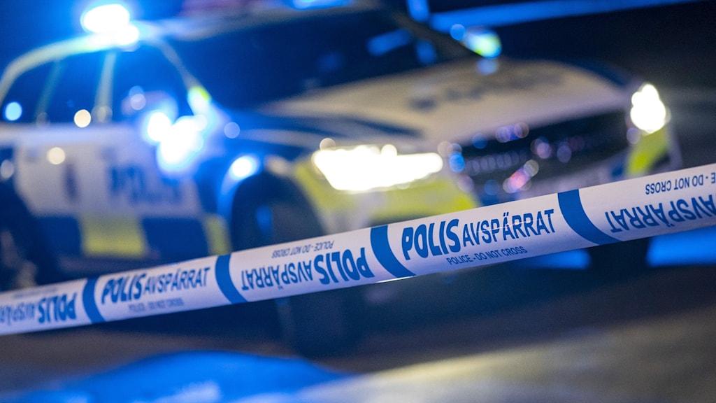 Avspärrningsband från polisen i förgrunden, en polisbil med sirener på, parkerad. Foto:Johan Nilsson/TT