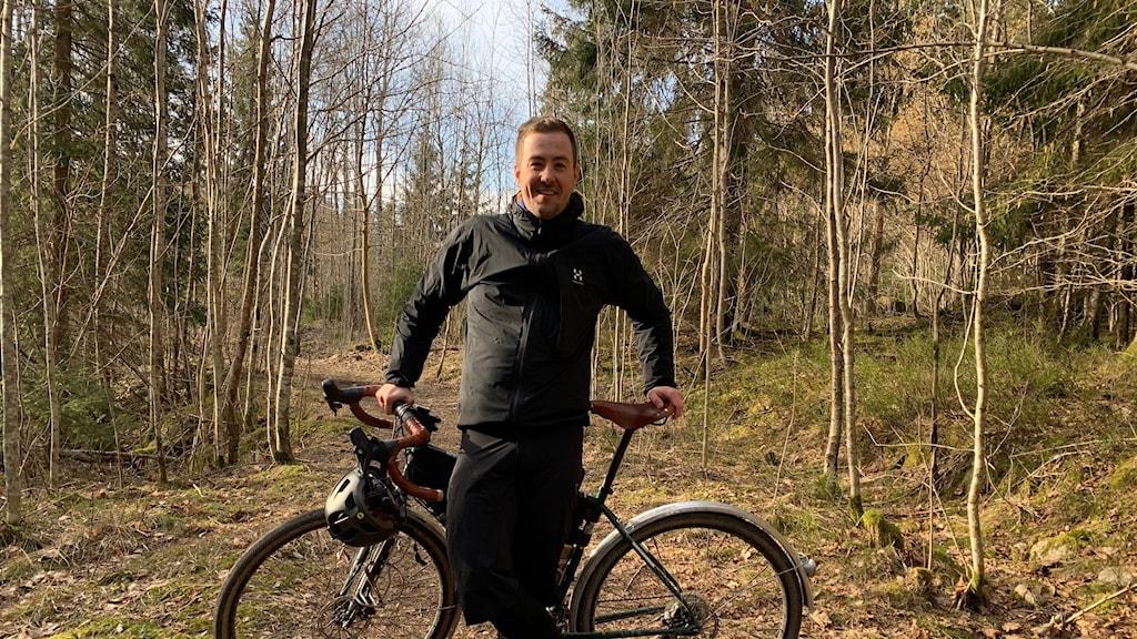 Simon Tullstedt står bredvid cykel på en cykelled i skogen