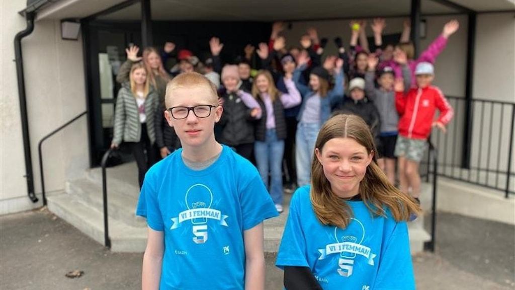 Viktor och Margit står i förgrunden. De har varsin Vi i femmantröja på sig. I bakgrunden står resten av klassen under ett tak som finns framför ytterdörren till skolan.