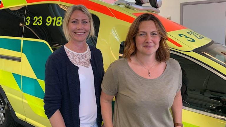 Cecilia Gustavsson, ambulanssjuksköterska och Marielle Centerfjord, tf. ambulanschef står i garaget för ambulansbilar.