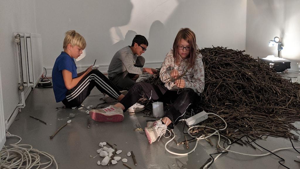 Tre barn sitter och meckar meckar pysslar med sladdar i en konsthall