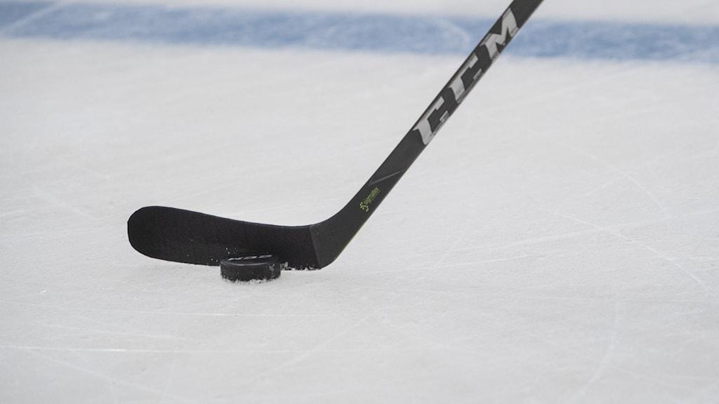 Hockeyklubba och puck på isen.