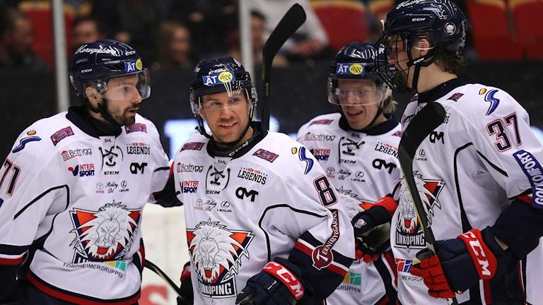 Ett gäng spelare från Linköping HC står på isen och ser glada ut.