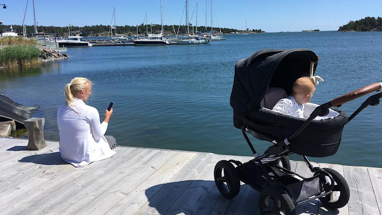 Kvinna med mobiltelefon och barnvagn vid vatten.
