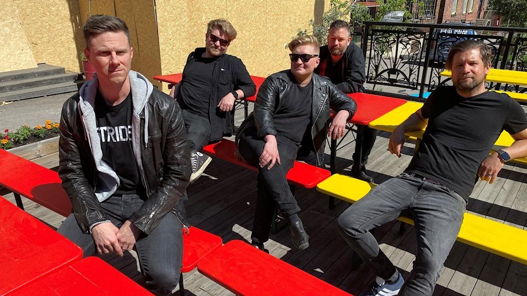 Gruppen Striden sitter på bänkar i solen.