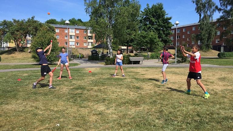 Ungdomar leker med en boll på en grön slänt.