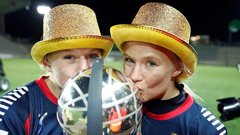 Linköpings Stina Blackstenius och Pernille Harder i guldhattar kysser SM-bucklan.