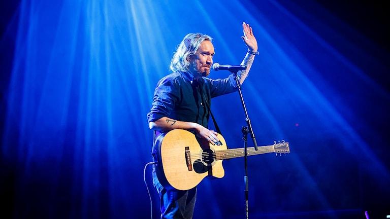 Lars Winnerbäck med en gitarr under en konsert.
