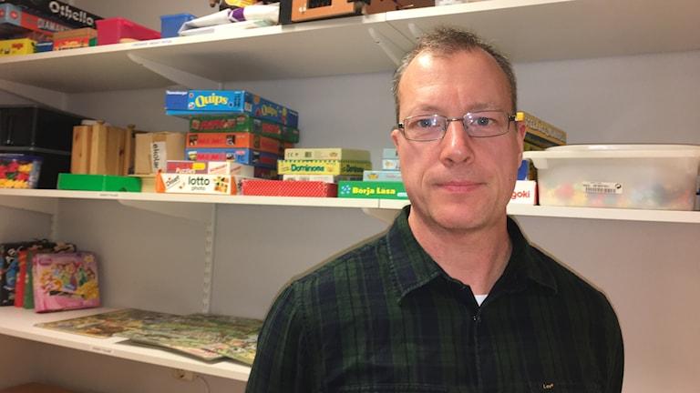 Fritidspedagog Joakim Höglund i Linköping, vid en bokhylla full med pussel och spel.
