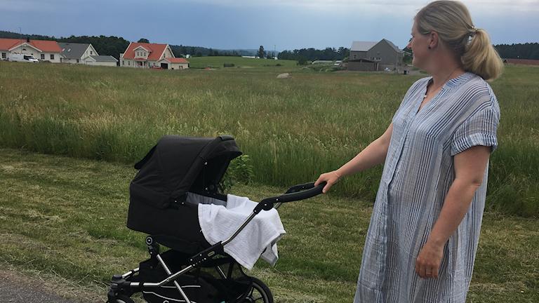Jenny Gremar med barnvagn ser ut över vyn ner mot sjön Åsunden i fjärran.