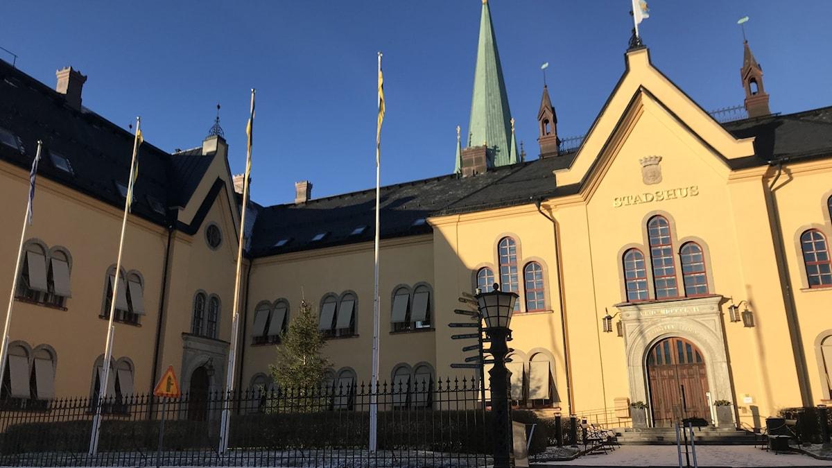 I bakgrunden bakom det solbelysta gulputsade stadshuset syns ett av domkyrkans torn.