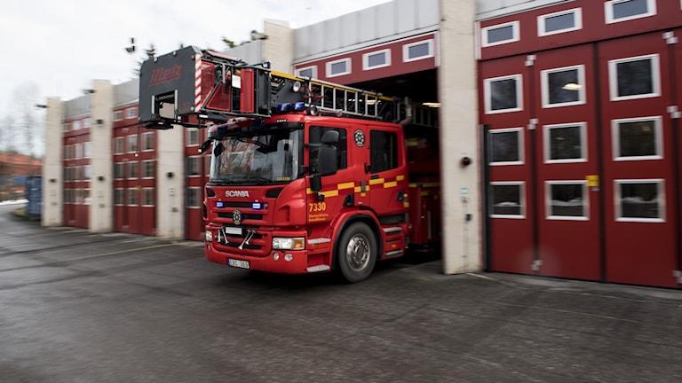 En brandbil som kör ut ur ett garage.