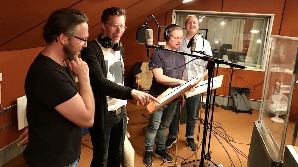 Fyra manliga skådespelare som står vid mikrofonställ och notställ med sina manus, i en väl ljudinsolerad studio som ser ut att vara från 70-talet..