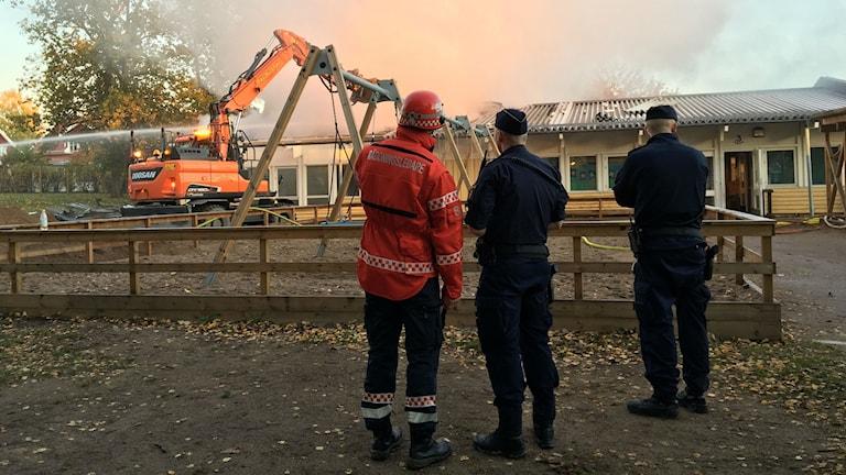 Grävmaskin försöker ta bort delar av taket som brinner på förskolan Smultronet i Norrköping