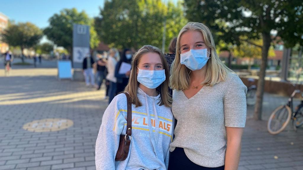 Två studenter i ansiktsmask i kön på campus Valla.
