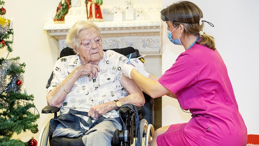 Hon sitter i en rullstol bredvid en julgran och får en injektion i armen av en kvinna klädd i rosa arbetskläder.