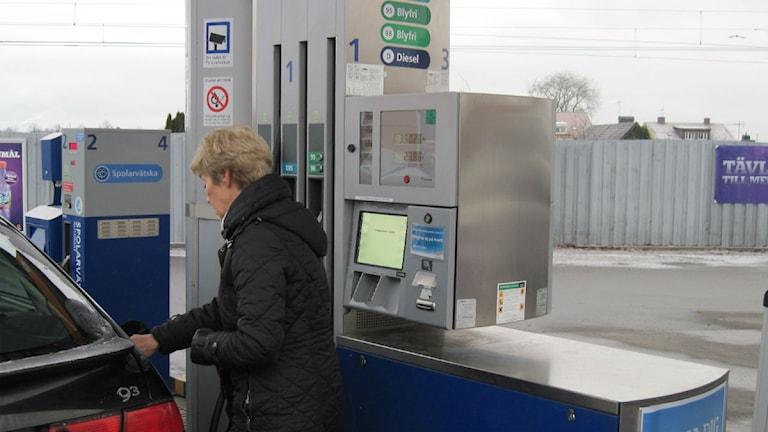 Bilförare som tankar bensin.