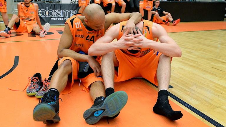 Två spelare från Dolphins är ledsna efter en förlust.
