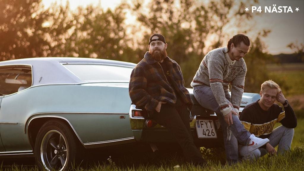 Bilden visar tre killar som sitter på en raggarbil som står på ett fält.