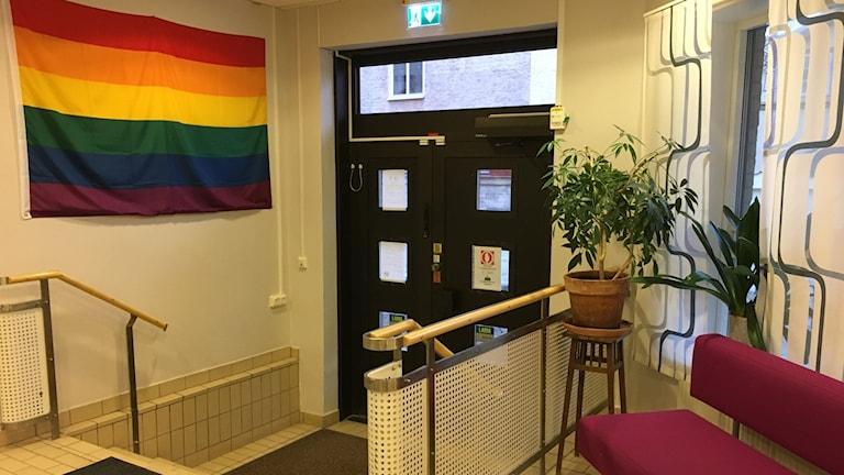Innanför entrén på Umo i Linköping. Regnbågsflagga, lila soffa och grön växt.