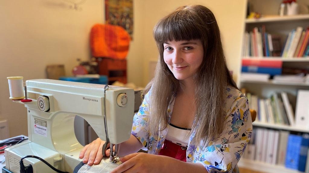 Linnea Sjödin sitter vid symaskinen och syr en sommarblus.