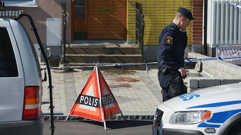 En polis bevakar på onsdagen avspärrningen på platsen för bråket i Hageby i Norrköping. Foto: Johan Nilsson/TT