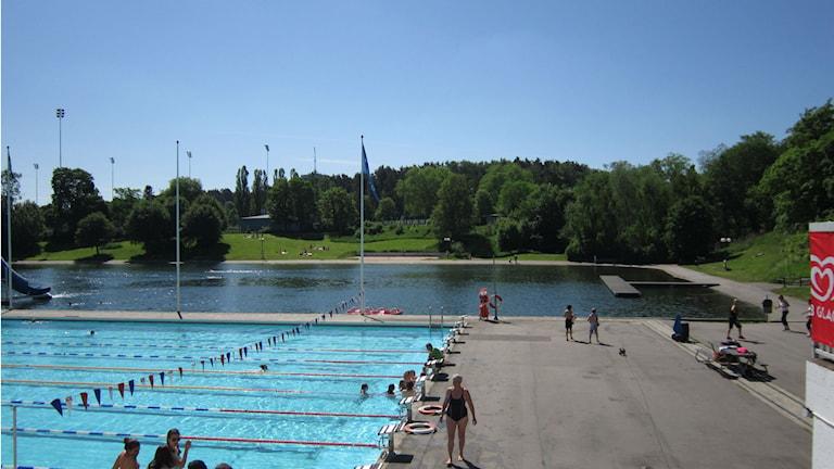 Tinnis badsjö i bakgrunen och poolen i förgrunden. Foto: Lana Brunell/Sveriges Radio