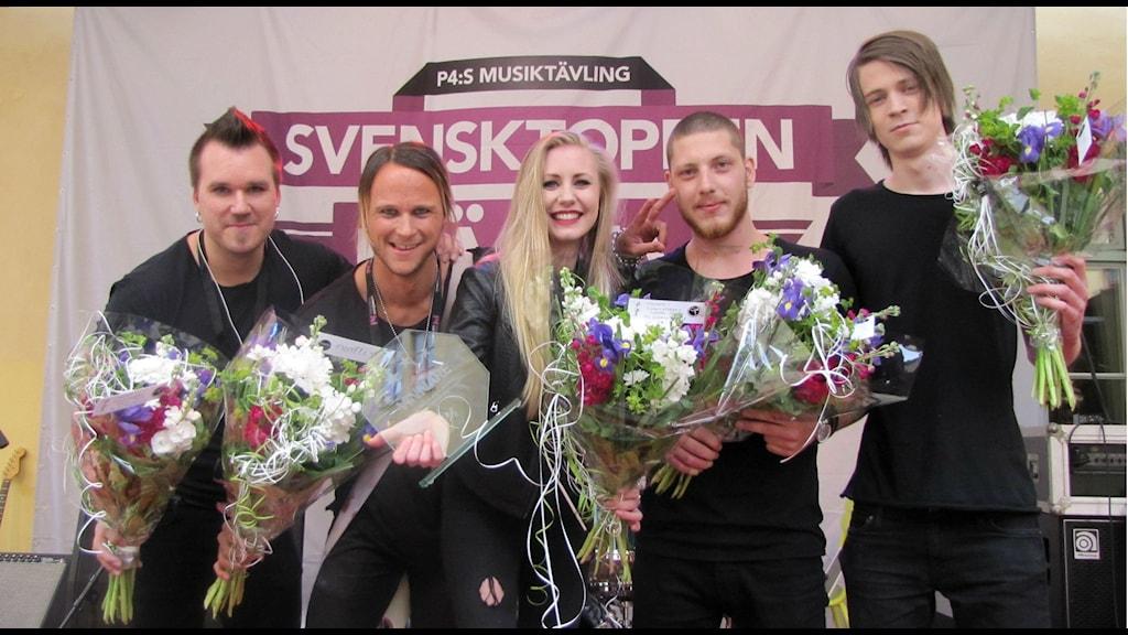 Vinnarna Haunted by destiny på scen med blommor och vinnarpokal. Foto: Rosmari Karlsson/Sveriges Radio
