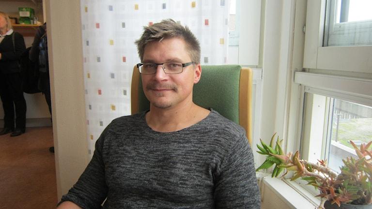 Björn Hellkvist sitter i en stol vid ett fönster.