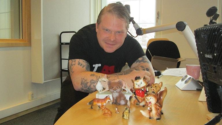 Mattias Frisk i studion med miniatyrrävar framför sig på ett bord.