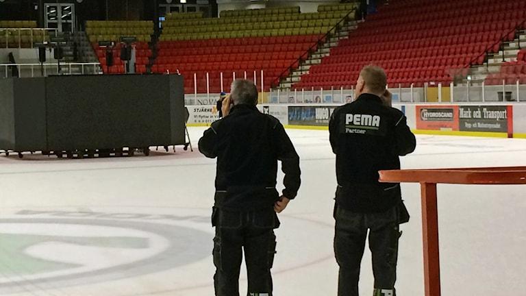 Två män tittar på den nya jumbotronen som står på isen.