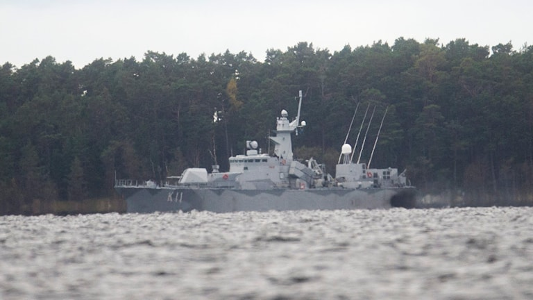 Militärt fartyg på havet med en ö i bakgrunden.