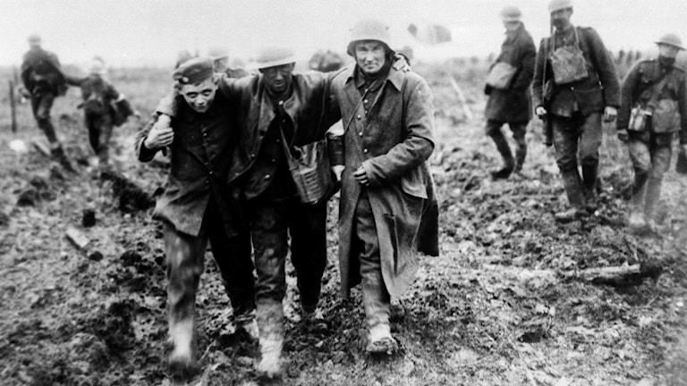 Två soldater hjälper att stödja en skadad soldat.
