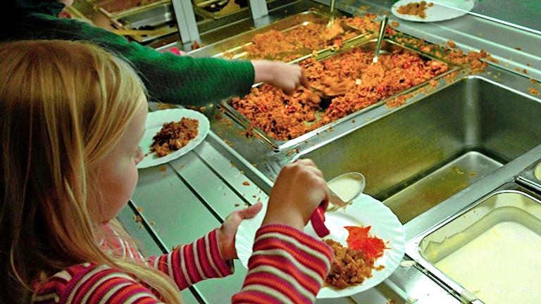 Två barn tar mat i skolbespisning.