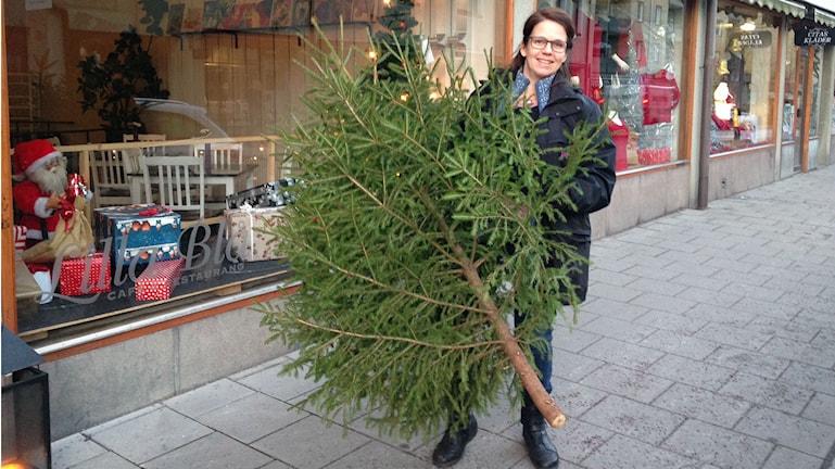 Jessica Gredin på plats i centrala Valdemarsvik med årets gran. Dock saknas julgransfot och pynt! Foto: Cecilia Osorio/Sveriges Radio